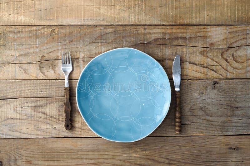 Голубые нож и вилка плиты на деревенском деревянном столе Обедать предпосылка стоковое фото rf