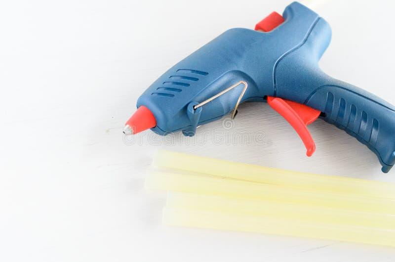Голубые оружие клея и горячие плавят штанги на белой предпосылке стоковое изображение