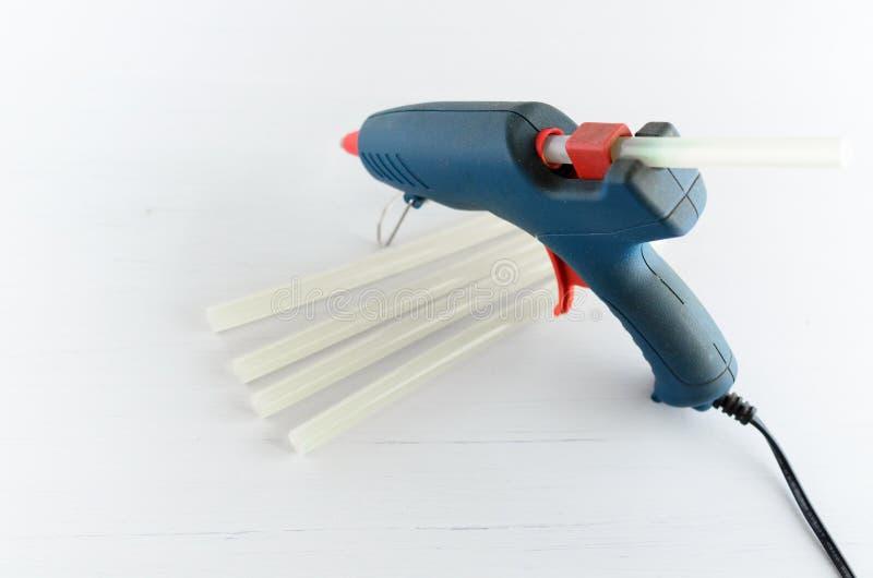 Голубые оружие клея и горячие плавят штанги на белой предпосылке стоковые изображения