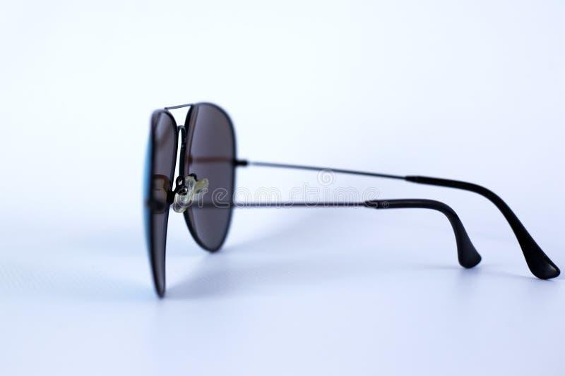 Голубые отраженные солнечные очки с анти--отражательным покрытием и УЛЬТРАФИОЛЕТОВАЯ защита на белой предпосылке стоковые изображения