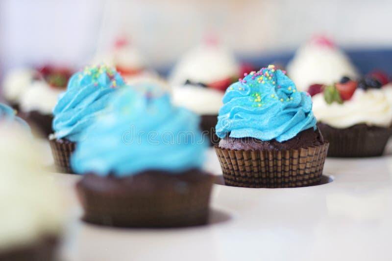 Голубые пирожные с брызгают на белой таблице стоковое изображение rf