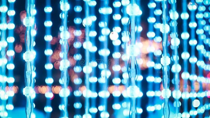 Голубые света строки, деревянное уличное освещение веселого рождества bokeh электрических лампочек предпосылки в уличном праздник стоковое изображение rf