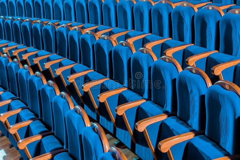 Голубые стулья плюша с деревянными подлокотниками в аудитории Пустая аудитория в театре стоковые изображения rf