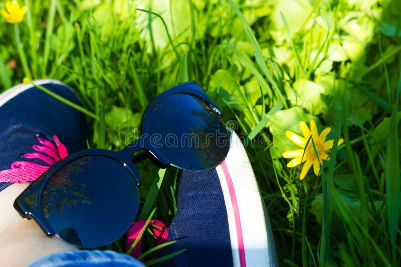 Голубые тапки и джинсы на ногах женщины сидя на gr стоковая фотография