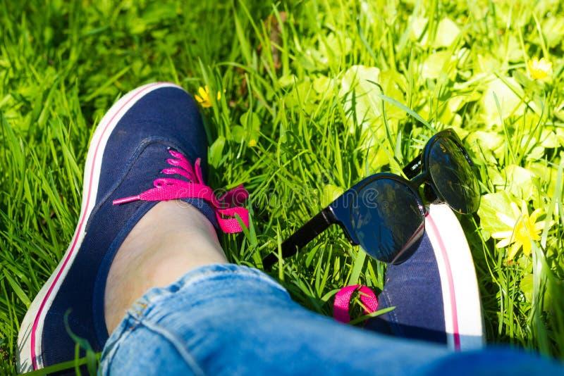 Голубые тапки и джинсы на ногах женщины сидя на gr стоковые фотографии rf