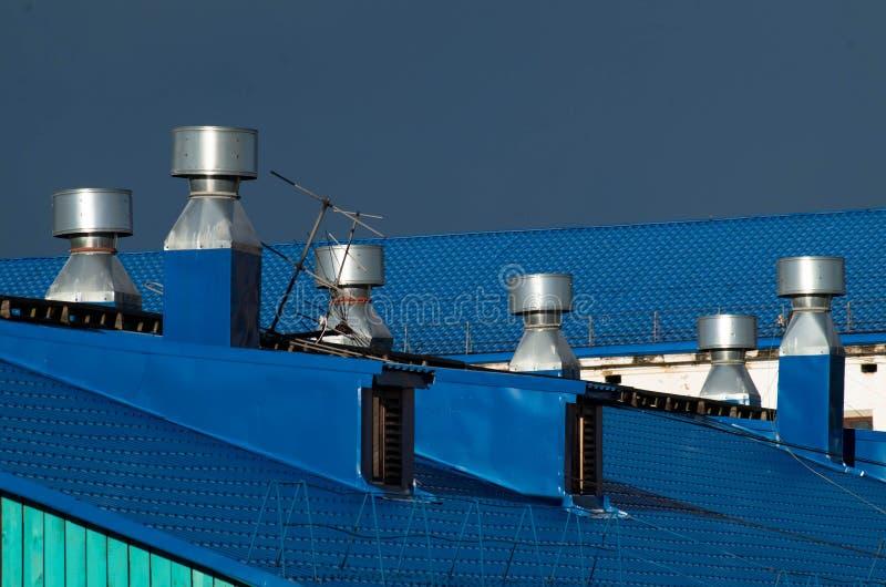 Голубые трубы крыши и вентиляции на ем стоковое изображение rf