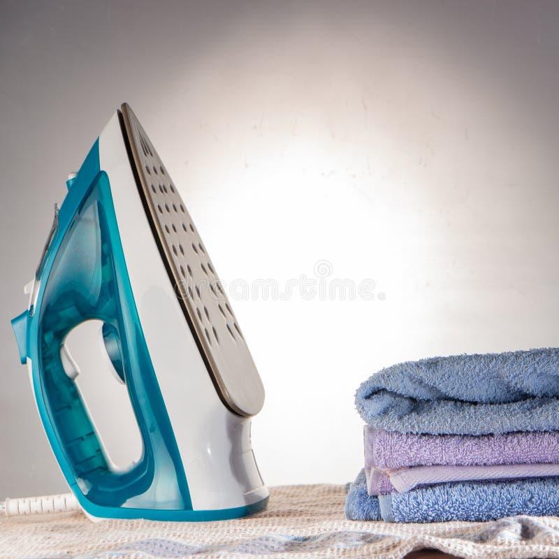 Голубые утюг и рубашка на концепции бытового прибора рубашки утюжа доски электрической стоковая фотография