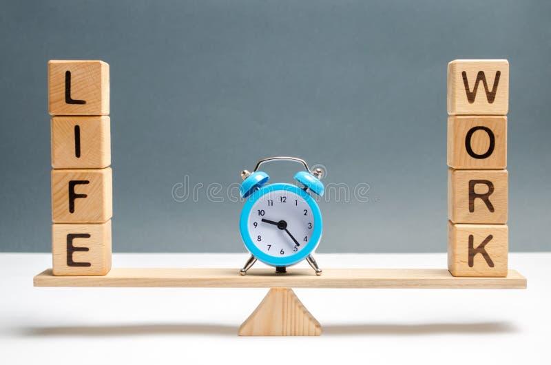 Голубые часы между жизнью слов и работой в масштабах выбор между жизнью и работой Концепция обращать внимание стоковые фото