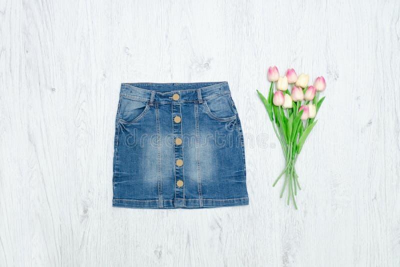 Голубые юбка джинсовой ткани и букет тюльпанов женщина состава способа стороны принципиальной схемы красотки голубая яркая стоковые фото