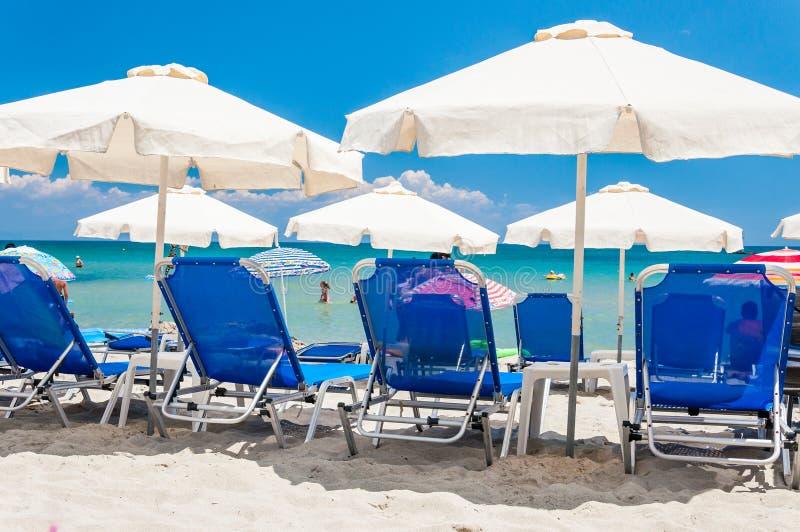 Голубые deckchairs, белые парасоли зонтиков, отдыхая туристы на пляжах греческого курортного города Paralia с теплым Эгейским мор стоковое фото rf