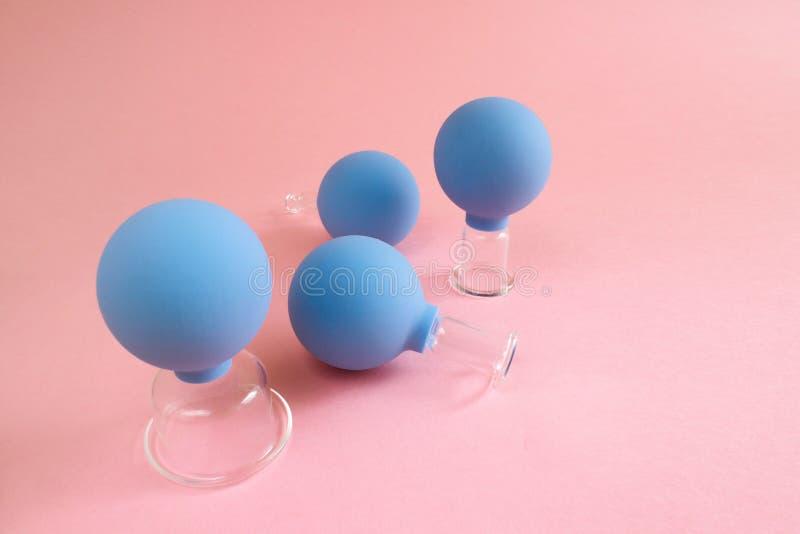 4 голубых косметических опарника вакуума для массажа тела и стороны различных размеров сделанных из стекла и резины на розовой пр стоковое фото rf