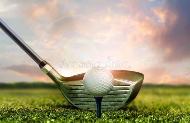 Гольф-клуб и шарик на траве под светами неба захода солнца стоковое фото rf