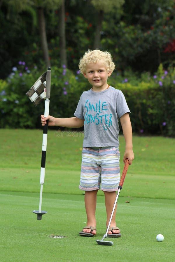 гольф мальчика играя детенышей стоковые фото