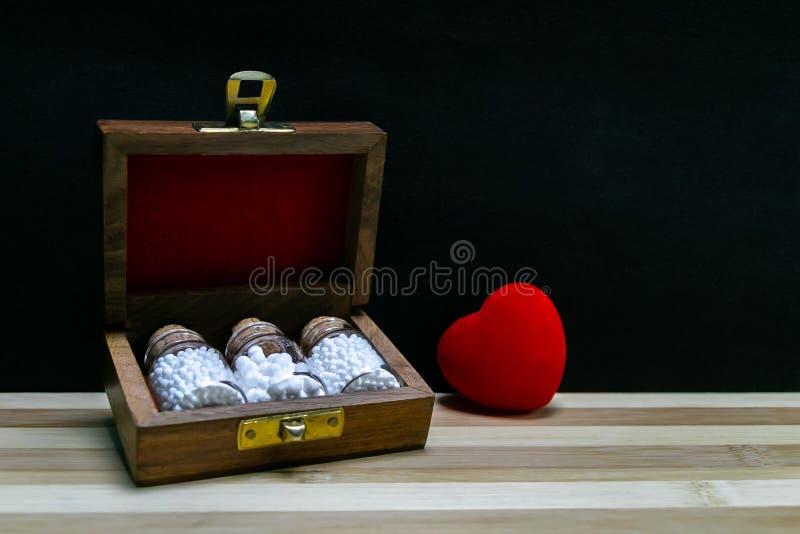 Гомеопатические медицины для здорового сердца - старой деревянной коробки с винтажными бутылками стекла гомеопатии таблеток и кра стоковая фотография rf