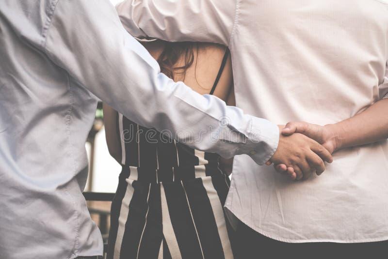 Гомосексуальная женщина объятия человека пока держащ руки с секретным любовником стоковые фотографии rf