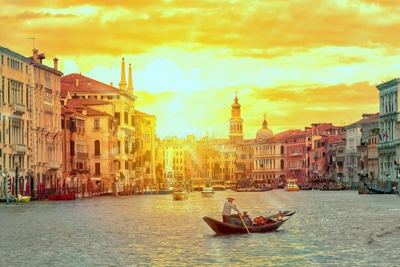 Гондола с gondolier около канала моста Rialto грандиозного в Венеции, Италии во время захода солнца Открытка Венеции туризм голуб стоковая фотография rf