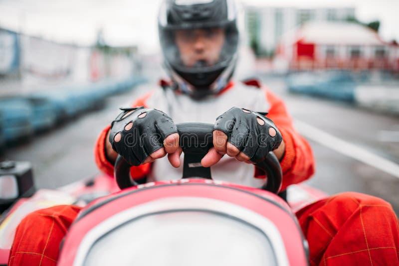 Гонка Karting, идет водитель тележки в шлеме стоковое изображение