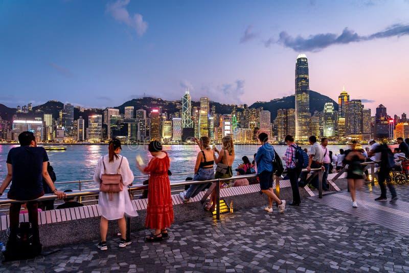 Гонконг, Китай - люди наслаждаясь взглядом стороны гавани города стоковое фото