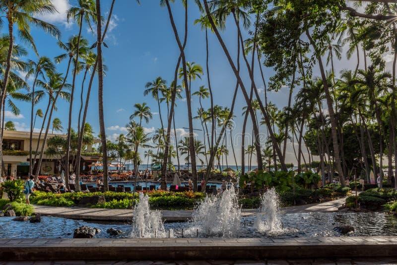 Гонолулу, Гавайские островы декабрь 13, 2018: Взгляд от лобби Hilton гавайского Village's главного фонтана, пальм и бассейна стоковое фото rf