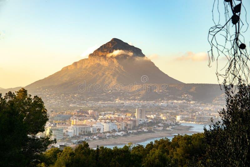 Гора в городе с красивым заходом солнца стоковые изображения