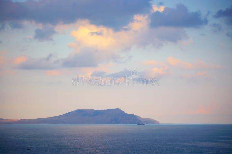 Гора в море на заходе солнца стоковая фотография
