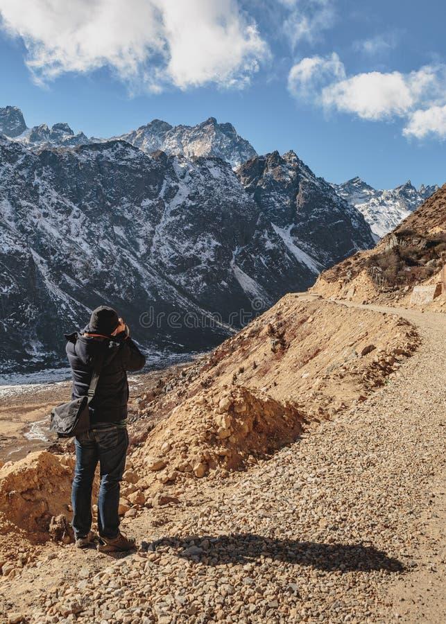 Гора черноты всхода туристов с снегом на верхнем и желтом каменистом грунте на долине Thangu и Chopta в зиме в Lachen стоковая фотография rf