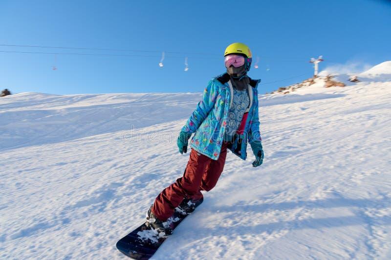 ГОРА ELBRUS, РОССИЯ - 30-ОЕ НОЯБРЯ 2017: Девушка сноуборда нося маску солнца и шарф едет вниз с высокогорного стоковое изображение rf