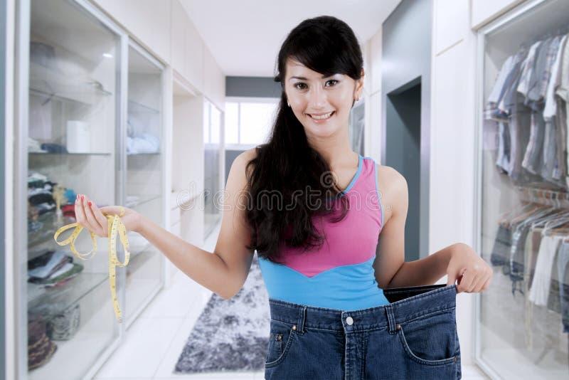 Гордая азиатская женщина показывая ее потерю веса стоковое изображение