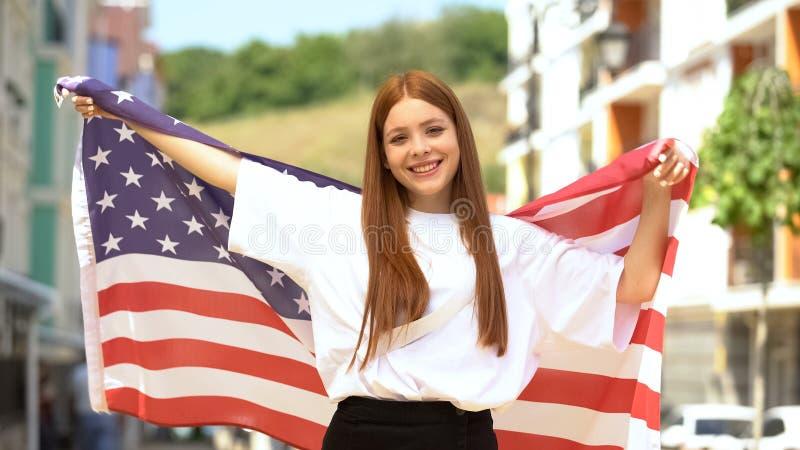 Гордая улыбка девушки-подростка, размахивая флагом США и улыбаясь на камеру, патриотизм стоковые изображения rf