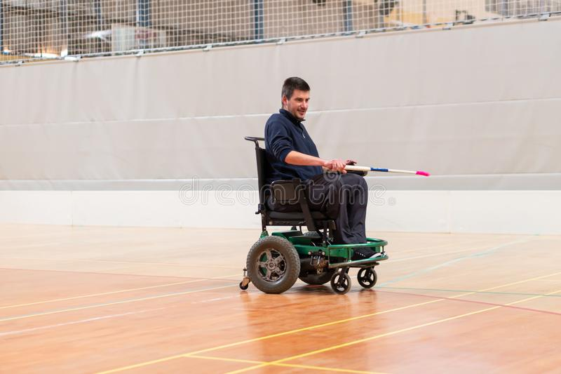 Гордый неработающий человек показывая с хоккейной клюшкой на электрической кресло-коляске играя спорт IWAS - Международная кресло стоковые фотографии rf