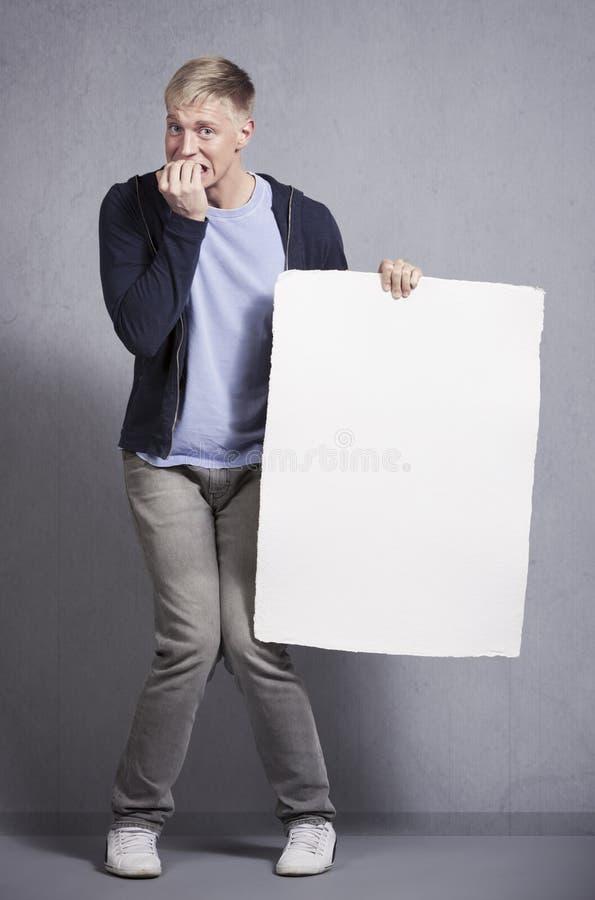 Горемычный человек держа белый пустой шильдик. стоковое фото rf