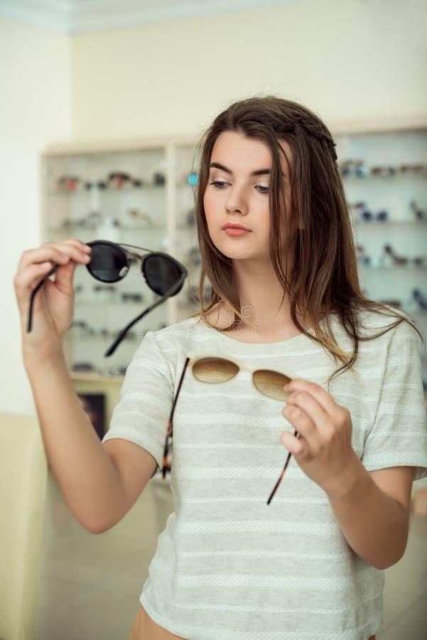 Горизонтальная съемка женственной молодой женщины на покупках, удерживании 2 пары стильных солнечных очков, смотря объективы и стоковое фото
