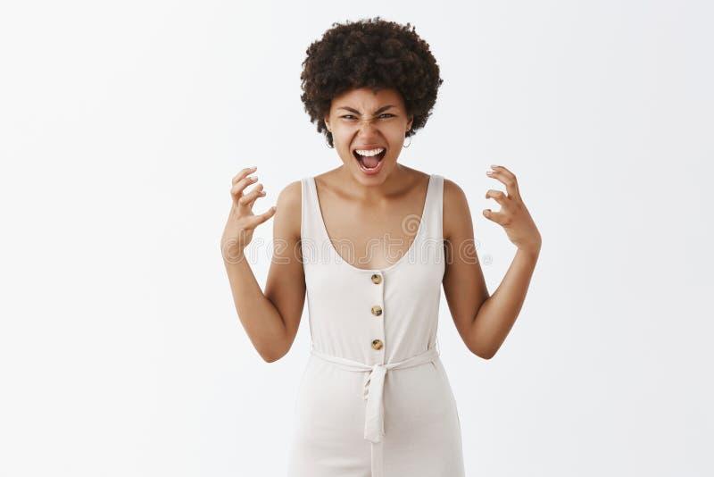Горизонтальная съемка злодействованной страшной женщины в белых прозодеждах с афро стилем причесок показывая жестами помоченные р стоковая фотография