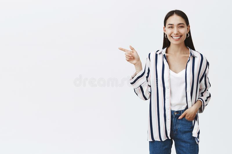 Горизонтальная съемка оптимистической счастливой красивой женщины в striped блузке и джинсах, держа руку в кармане и указывать стоковое изображение