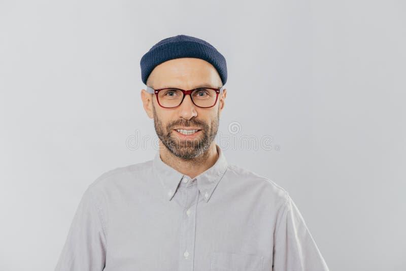 Горизонтальный взгляд довольного усмехаясь человека носит стекла, шляпу и рубашку, удовлетворяемый с хорошими новостями, моделями стоковые фотографии rf