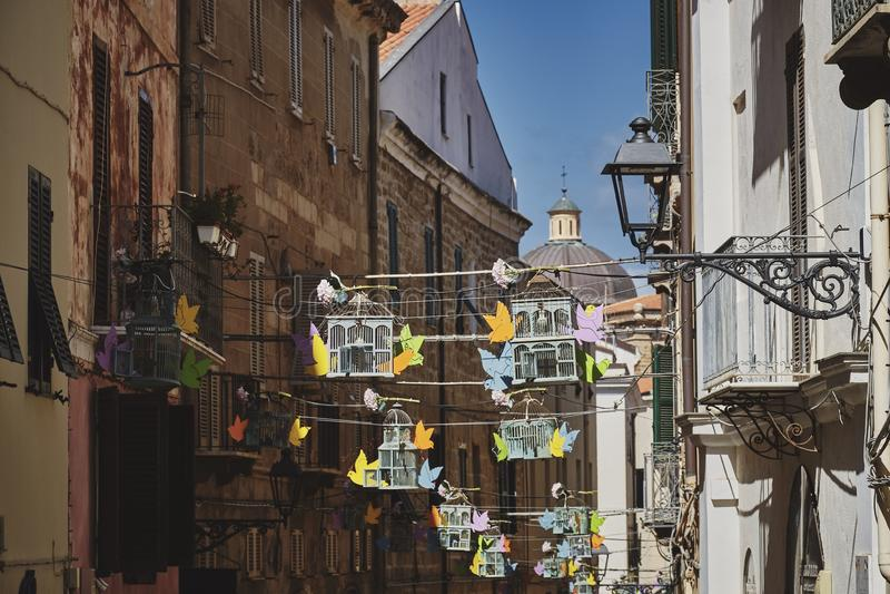Горизонтальный выстрел из висячих птиц между домами в старом районе Италии стоковые изображения
