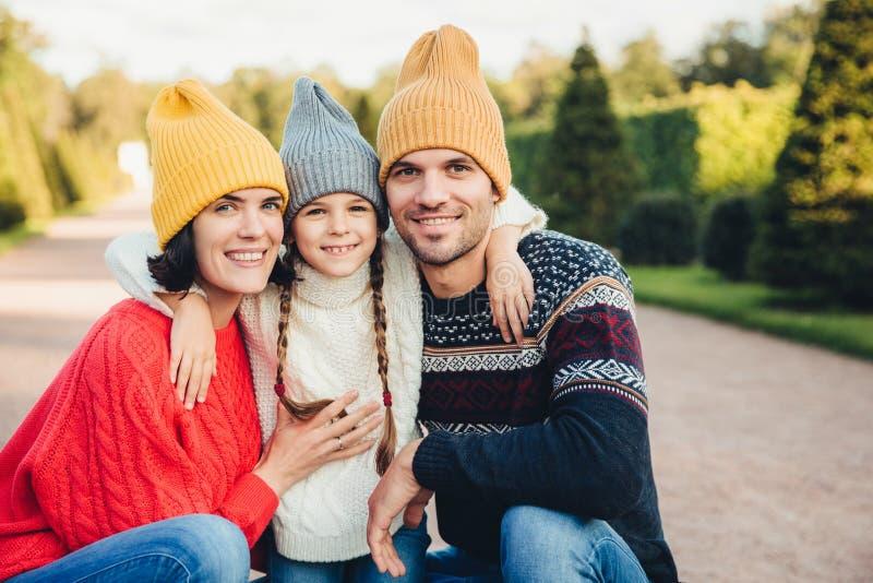Горизонтальный портрет дружелюбного ласкового одина другого объятия семьи, связанных ноской крышек и свитеров, идет совместно, им стоковое фото