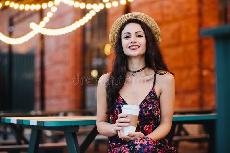 Горизонтальный портрет красивой женщины с составом одел в соломенной шляпе и платье, сидящ на террасе, чувствуя релаксация, havin стоковое изображение rf