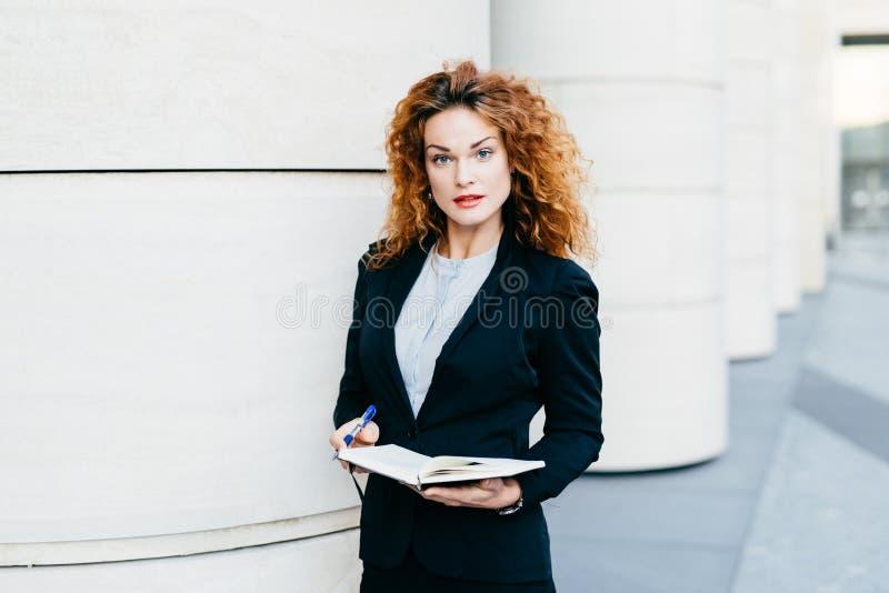 Горизонтальный портрет серьезной милой коммерсантки с вьющиеся волосы, тонкими бровями и вьющиеся волосы, нося черным костюмом и  стоковая фотография rf