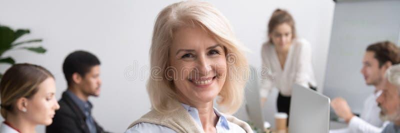 Горизонтальный портрет фото старшей коммерсантки усмехаясь смотрящ камеру стоковое фото rf