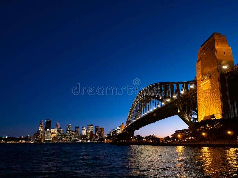 Горизонт города моста и Сиднея гавани вечером против яркого темно-синего неба стоковое изображение