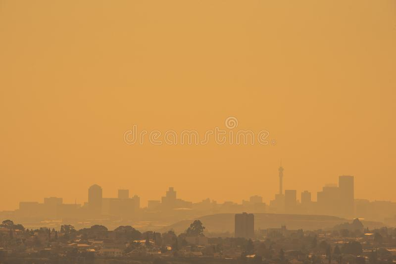 Горизонт Йоханнесбурга silhouetted против золотого неба стоковые фото