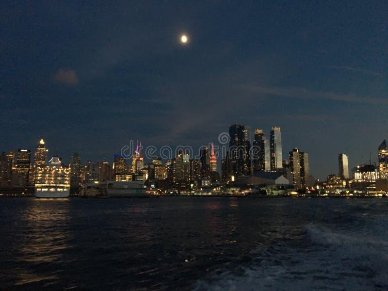 Горизонт Манхаттана с луной на ноче стоковые фото