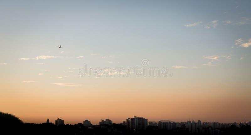 Горизонт Сан-Паулу с самолетом принимая полет стоковые изображения rf