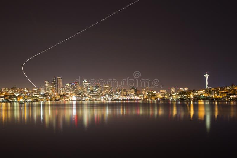 Горизонт Сиэтл к ноча с тропкой самолета стоковое изображение
