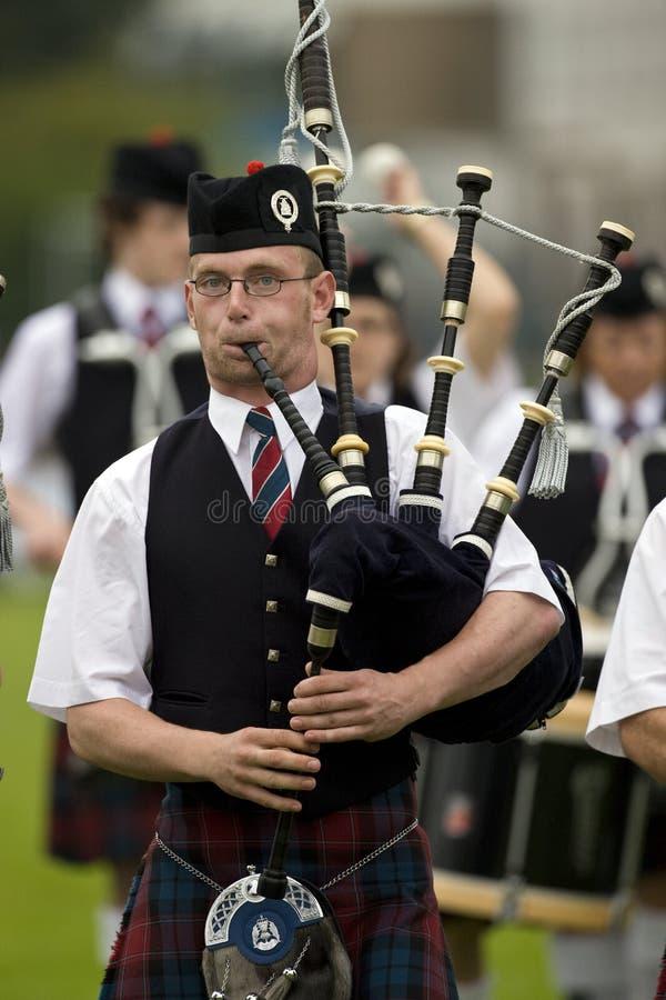 гористая местность Шотландия игр волынок стоковая фотография rf