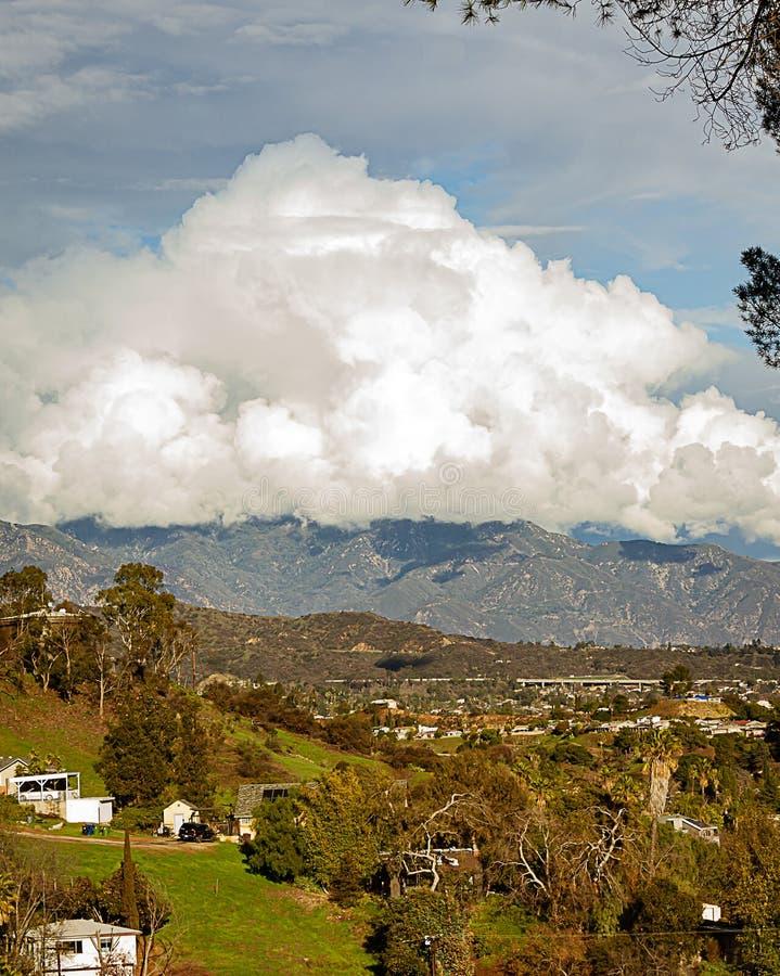 Горная цепь домов горного склона с огромными облаками nimbus кумулюса стоковые фото