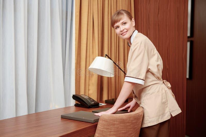 Горничная аранжируя канцелярские принадлежности гостиницы стоковое изображение rf