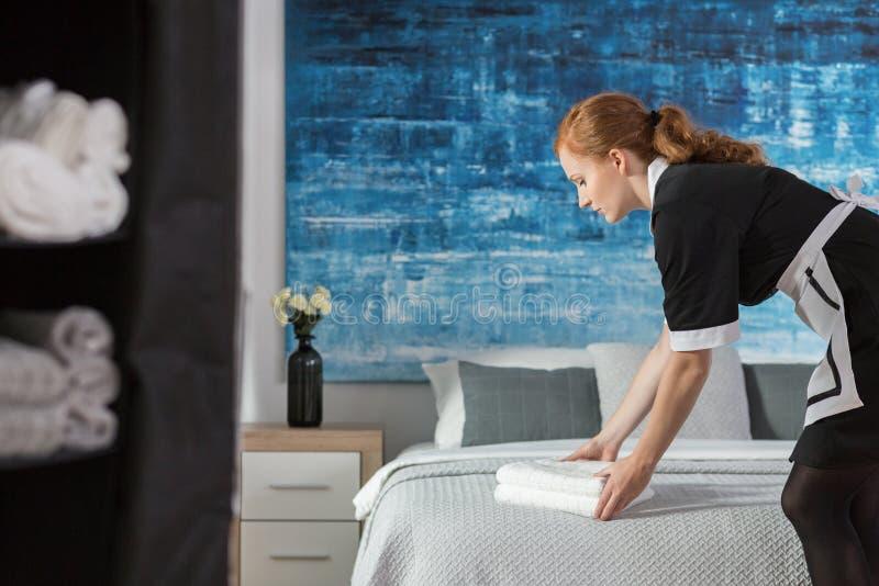 Горничная кладя полотенца на кровать стоковое фото