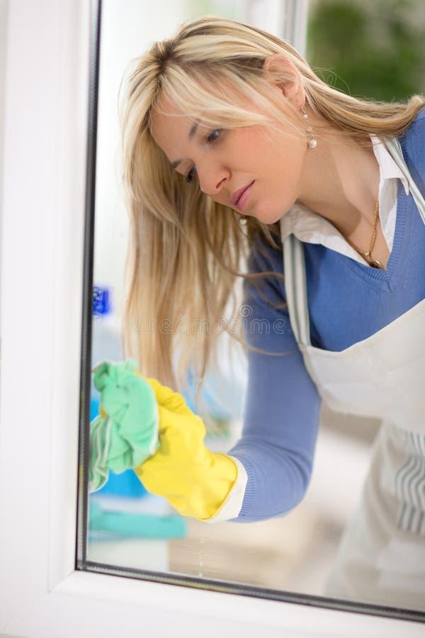 Горничная очищает окно стоковое фото